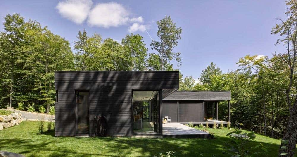 This black house is set well on the well-maintained lawn area and is surrounded by mature trees.