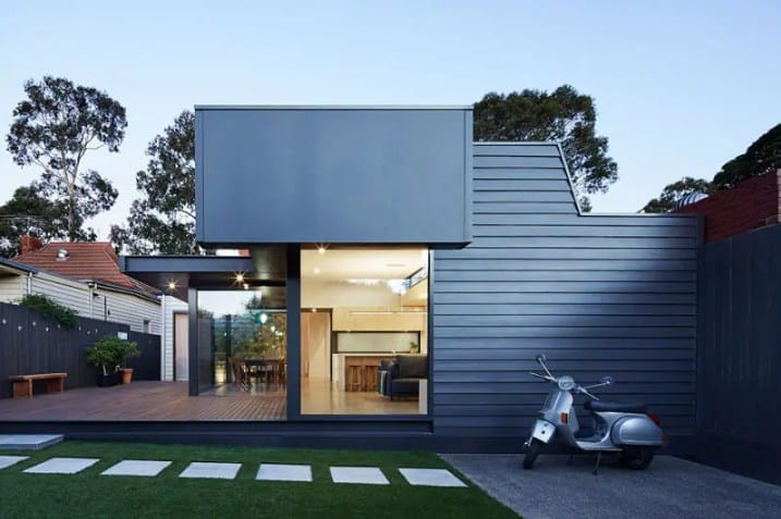 This home features a black exterior, a deck and a nice lawn area with a walkway.