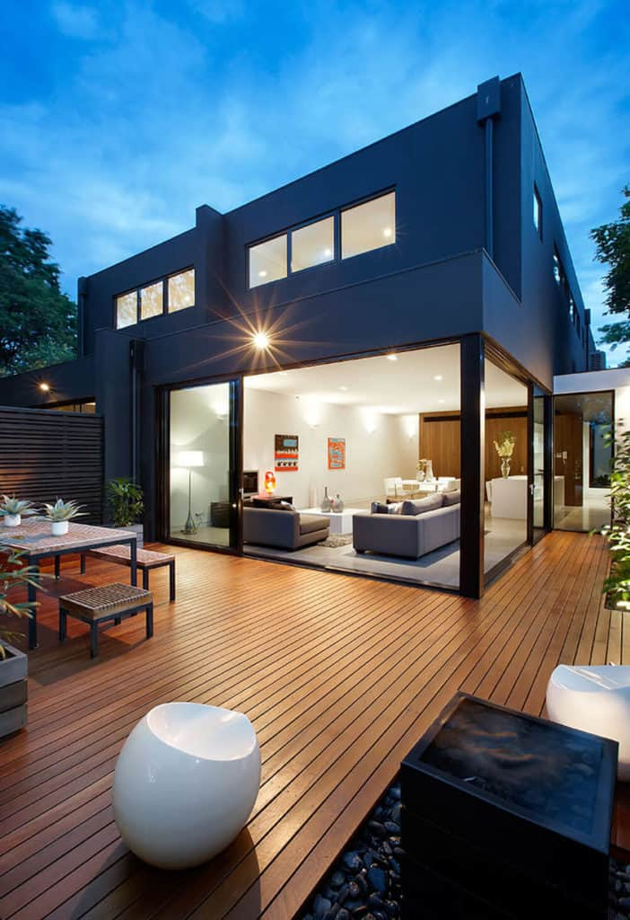 A modern black house featuring a deck with a square dining nook outside.