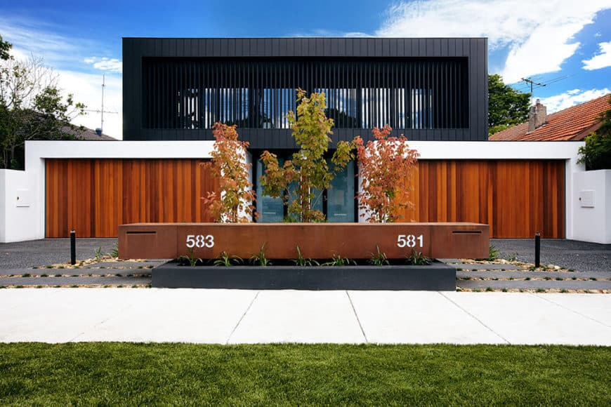A beautiful contemporary house with a large garage area and a fine walkway with a lawn area on the side.