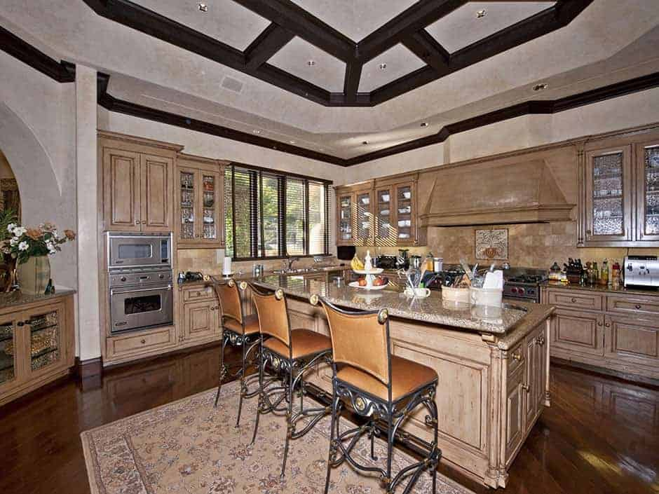 This kitchen boasts a beautiful ceiling along with wooden cabinetry and kitchen counters along with a center island featuring a breakfast bar counter.