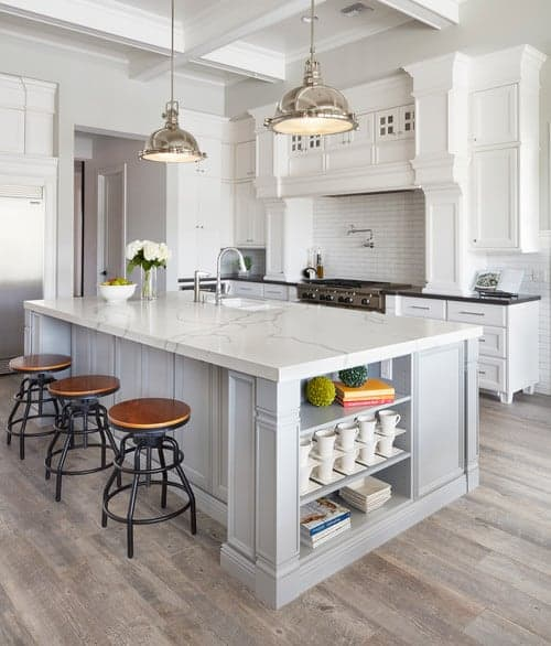 A focused shot at this kitchen's large center island with a lovely marble countertop lighted by a couple of pendant lights.