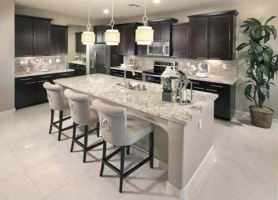 A classy kitchen featuring marble countertops on both kitchen counters and center island. The area is lighted by pendant lights and recessed lights.