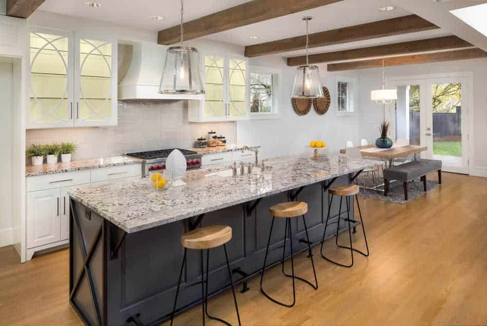 A single wall kitchen featuring a long island with a breakfast bar counter. The kitchen counter and center island both have marble countertops.
