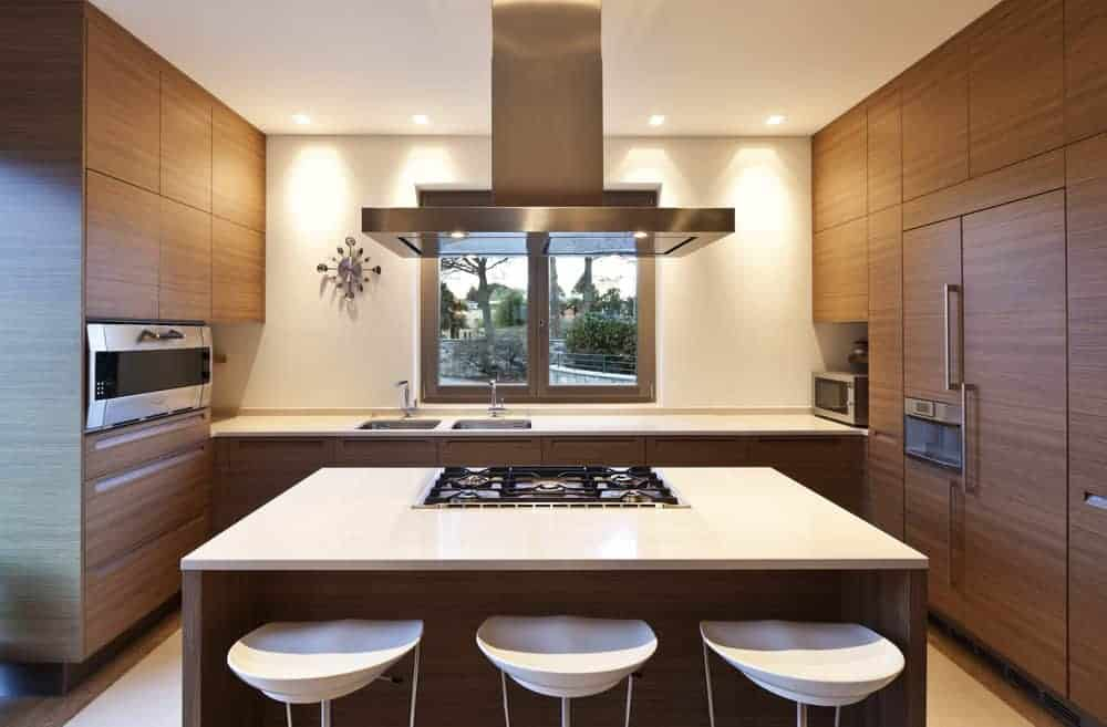 A small kitchen featuring brown kitchen counter and a center island, both have white countertops.