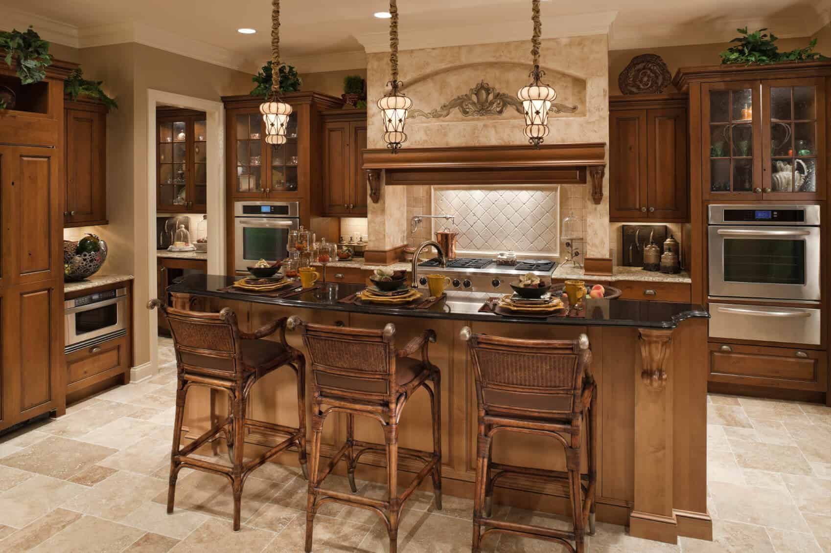 A brown kitchen featuring wooden cabinetry, kitchen counters and a center island with a breakfast bar counter lighted by pendant lights.