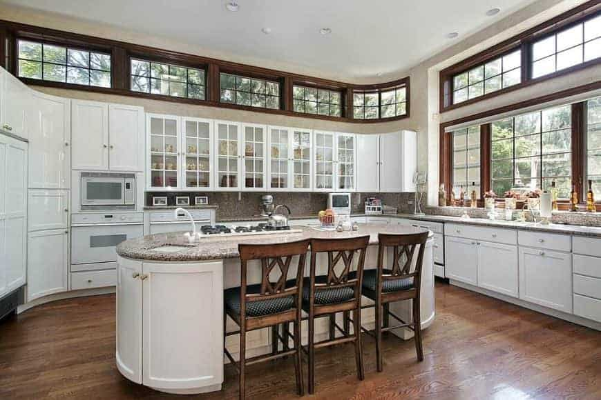 This kitchen offers a custom island with space for a breakfast bar, set on the hardwood flooring.