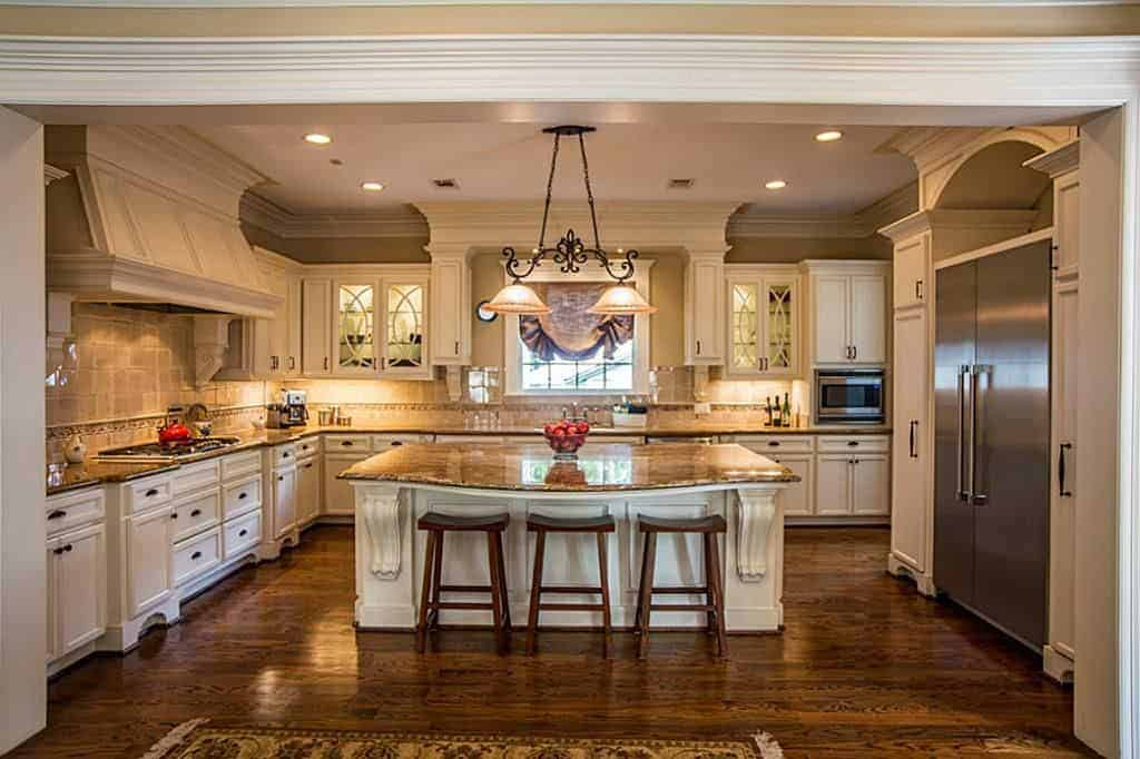 Large kitchen featuring white kitchen counters and a center island, both featuring marble countertops. The island has a breakfast bar counter.
