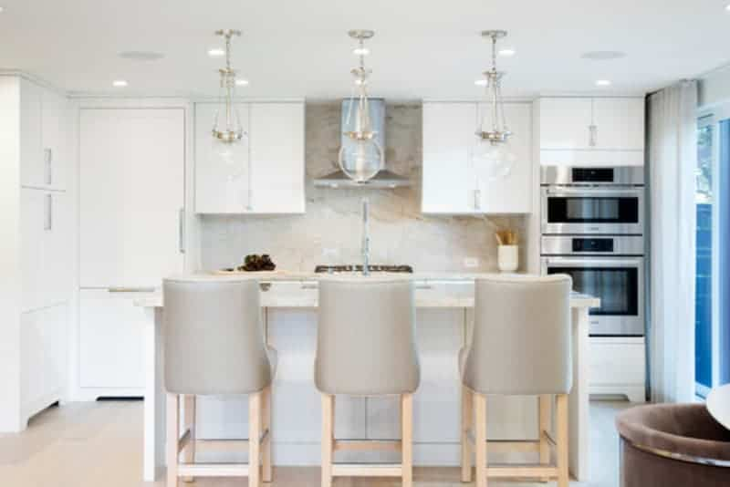 This kitchen features a small island with space for a breakfast bar. The pendant lights look lovely as well.