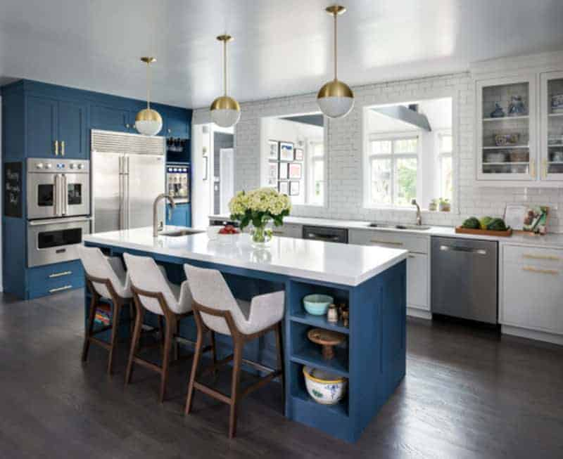 This kitchen features blue cabinetry and a blue island with space for a breakfast bar. The island features a white countertop.