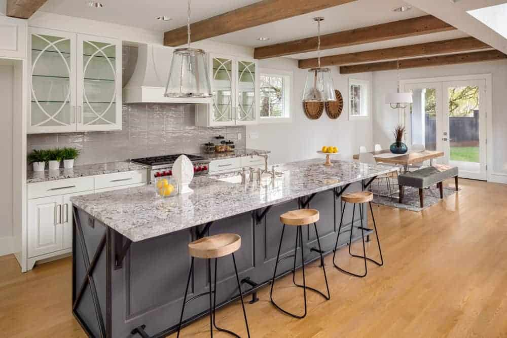 A single wall kitchen featuring a long island with a marble countertop and has a breakfast bar counter lighted by pendant lighting.
