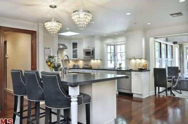 This kitchen offers a small island with space for a breakfast bar and is lighted by a pair of gorgeous lighting.
