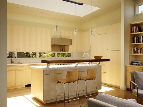 This kitchen features a skylight along with three pendant lights lighting the island with a breakfast bar counter.