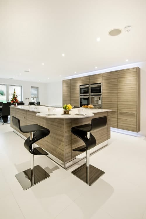 A kitchen featuring a white and brown color scheme. It has a large center island with separate space for a breakfast bar with stylish modern bar stools.