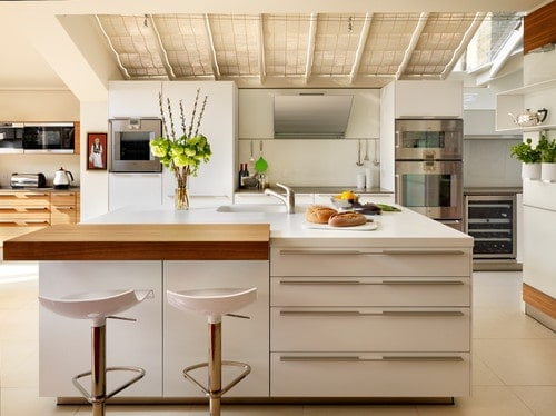 A close up look at this kitchen's separate breakfast bar counter on the side of the large white center island of the kitchen.