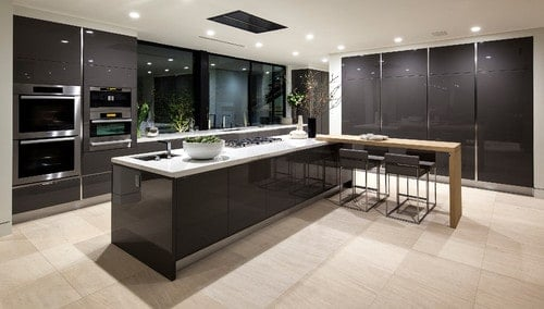 A black and white color scheme kitchen featuring a long center island with a separate breakfast bar island on the side.