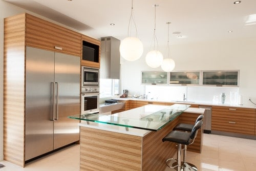 This kitchen offers a center island with a glass top breakfast bar counter.