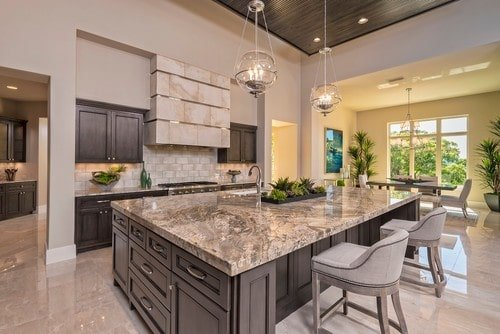 A single wall kitchen boasting a massive center island featuring a marble countertop and has space for a breakfast bar lighted by a couple of pendant lighting.