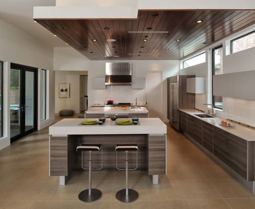 This kitchen offers two islands, one with space for a breakfast bar, and both has white countertops.