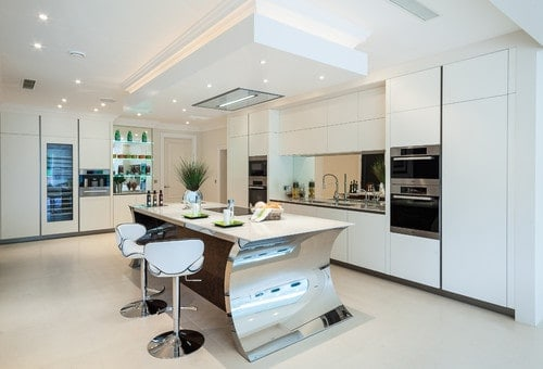 A large kitchen area with a white and silver color scheme and has scattered recessed lights on the ceiling. The kitchen also offers a contemporary island with space for a breakfast bar.