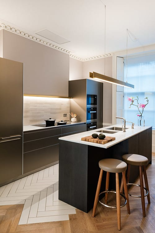 A single wall contemporary kitchen featuring herringbone-style flooring and a black center island with a white countertop and has space for a breakfast bar.
