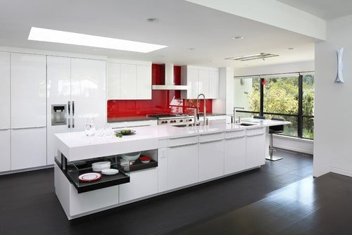A white modern kitchen with a red accent. It features a long center island with a breakfast bar counter on its side.