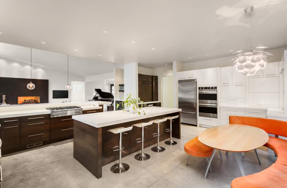 A beautiful white and brown kitchen featuring a breakfast bar island with modern stools along with a gorgeous dining nook with an orange accent seat.