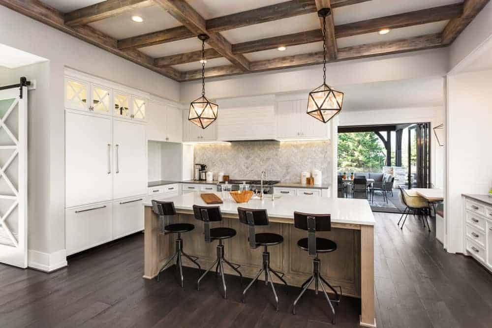 This kitchen features hardwood floors and a wooden coffered ceiling. The kitchen also offers an island with a marble countertop and has space for a breakfast bar lighted by pendant lights.
