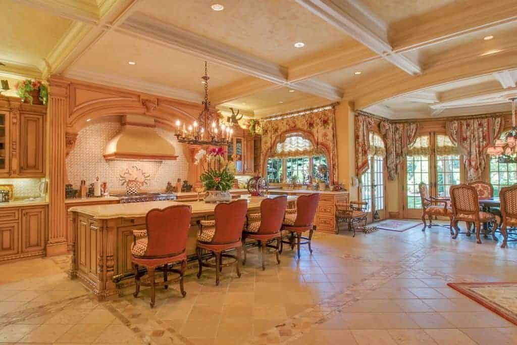 Large kitchen area with gorgeous flooring and ceiling along with brown cabinetry and kitchen counters. There's a long center island with a marble countertop and has space for a breakfast bar lighted by a gorgeous chandelier.