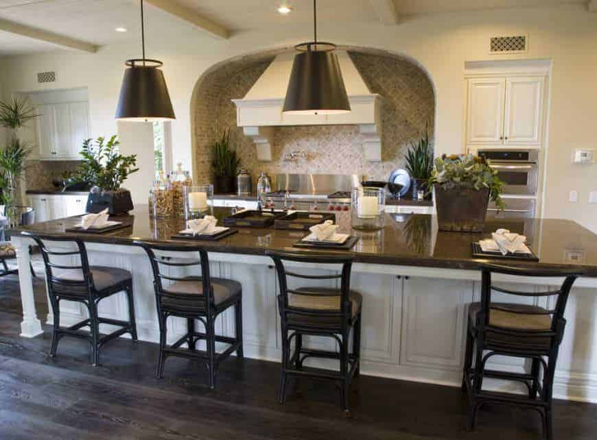 A single wall kitchen featuring a large center island set on the hardwood flooring. This island offers space for a breakfast bar lighted by large pendant lights.
