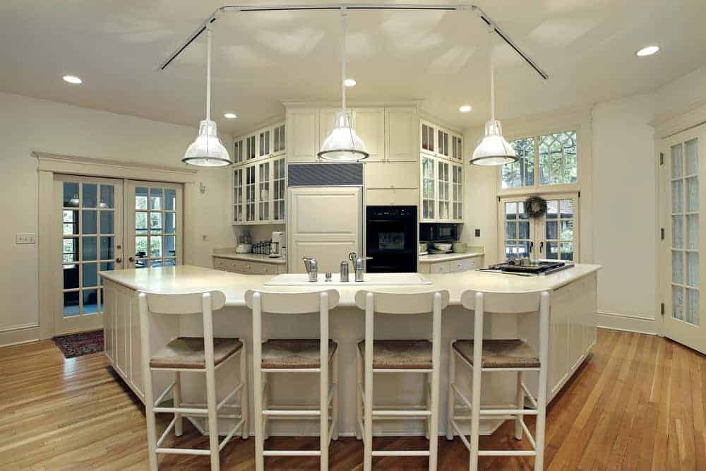 This kitchen offers a custom island with a marble countertop and has space for a breakfast bar set in the middle and is lighted by pendant lights.
