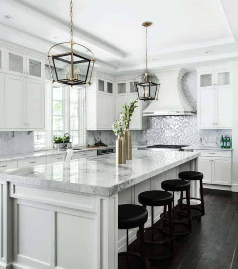White kitchen featuring marble countertops on both kitchen counters and center island. The island offers space for a breakfast bar.
