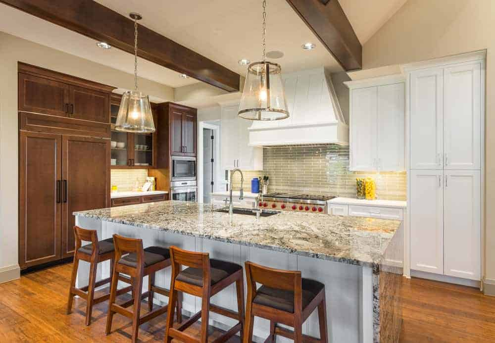 This kitchen features a large center island with a marble countertop lighted by pendant lights. The island offers space for a breakfast bar.