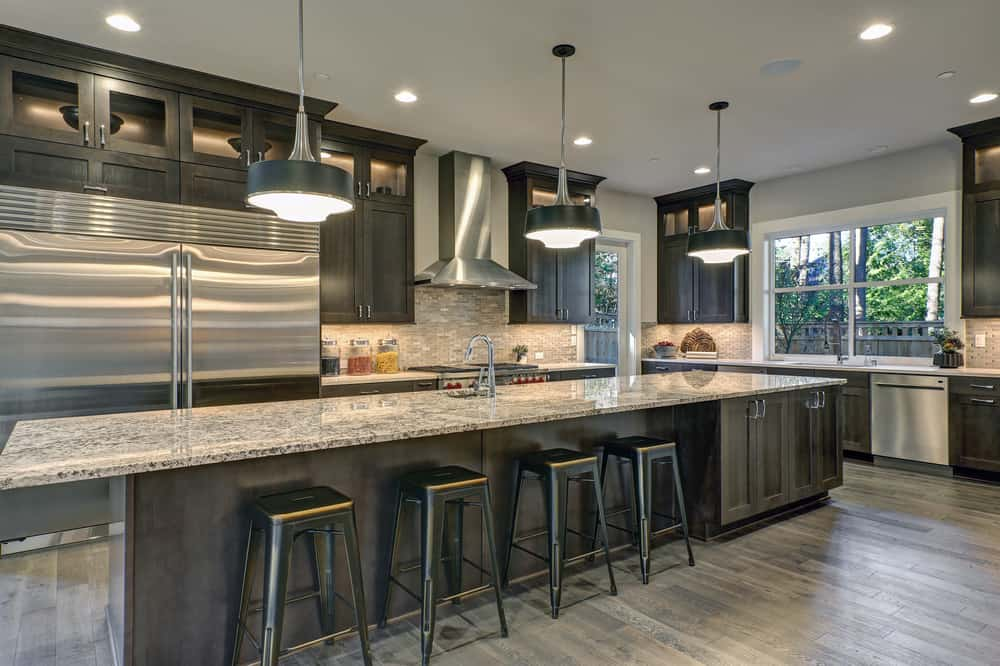 This kitchen features a long center island with a marble countertop and has space for a breakfast bar lighted by three pendant lights.