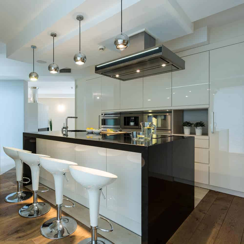 This kitchen features a stylish center island with a black countertop and has space for a breakfast bar paired with white modern bar stools.