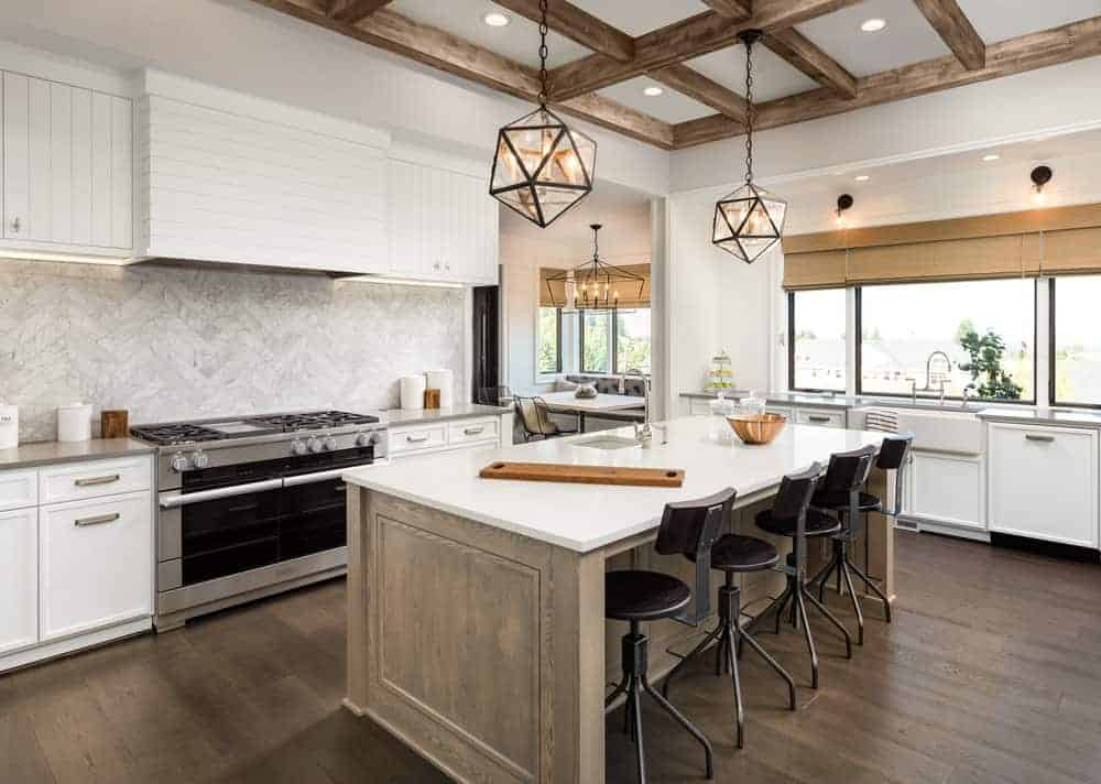 This kitchen boasts a stylish marble herringbone-style backsplash. It also has a center island with space for a breakfast bar lighted by two fancy ceiling lights.