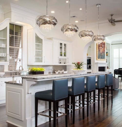 This kitchen features a long island with stylish marble countertop and has a breakfast bar counter lighted by fancy ceiling lights.
