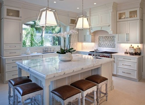 A white kitchen featuring white cabinetry and kitchen counters, along with a white center island with a white marble countertop and is lighted by two pendant lights.