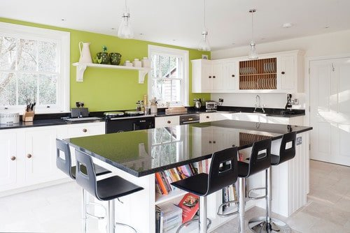 This kitchen features white, black and green color scheme and has a large center island with a breakfast bar and features built-in shelves below the countertop.