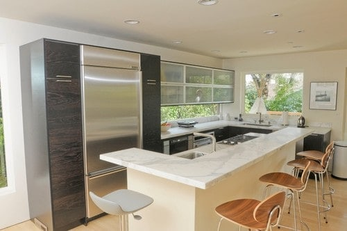 A small kitchen area featuring an island with a breakfast bar counter boasting a marble countertop.