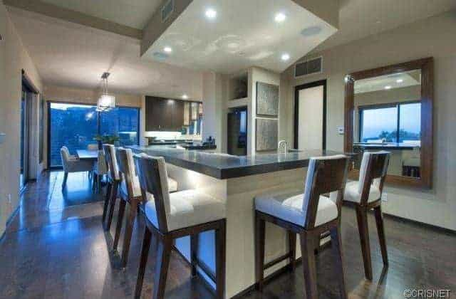 A custom kitchen featuring an island that offers a breakfast bar counter with seats set on the hardwood flooring.