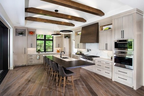 This kitchen features hardwood floors and a ceiling with exposed beams. It also offers a stylish center island with a breakfast bar.