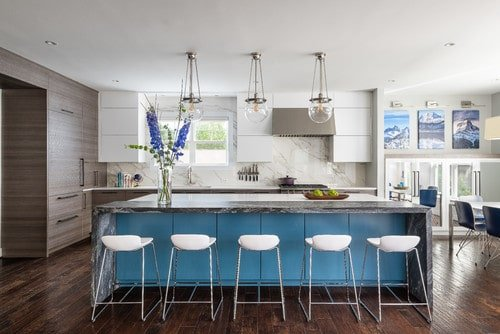 Spacious kitchen featuring a large center island with a marble countertop lighted by three pendant lights.