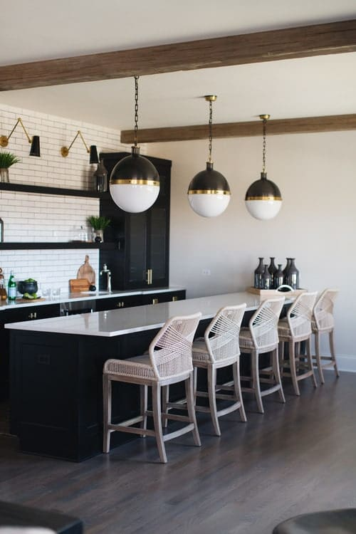 A single wall kitchen featuring espresso kitchen counter and center island, both with white countertops and has a breakfast bar lighted by gorgeous pendant lights.