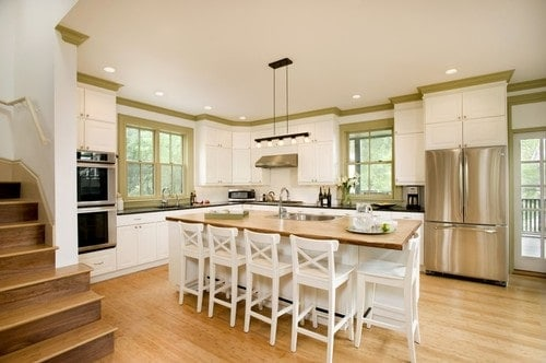 A bright kitchen featuring white cabinetry and kitchen counters, along with a center island with a wooden countertop.
