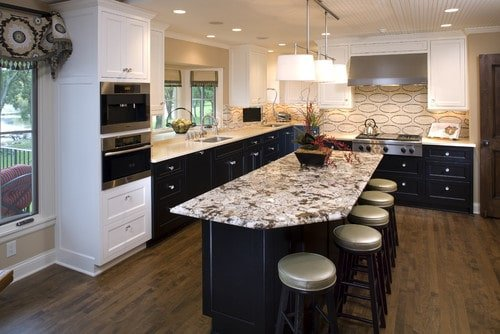 An L-shaped kitchen with hardwood flooring and white cabinetry. It offers a center island with a marble countertop and has space for a breakfast bar.