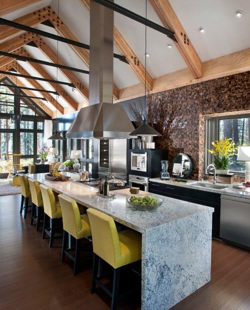 A single wall kitchen featuring a tall vaulted ceiling with exposed beams along with a marble center island with space for a breakfast bar.
