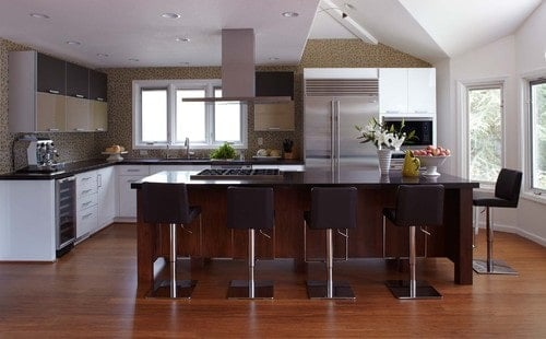An L-shaped kitchen featuring black countertops on both kitchen counters and the center island along with a breakfast bar with modern bar stools.