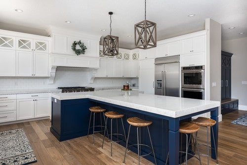 This kitchen offers a custom T-shaped blue center island with a white countertop and has space for a breakfast bar.