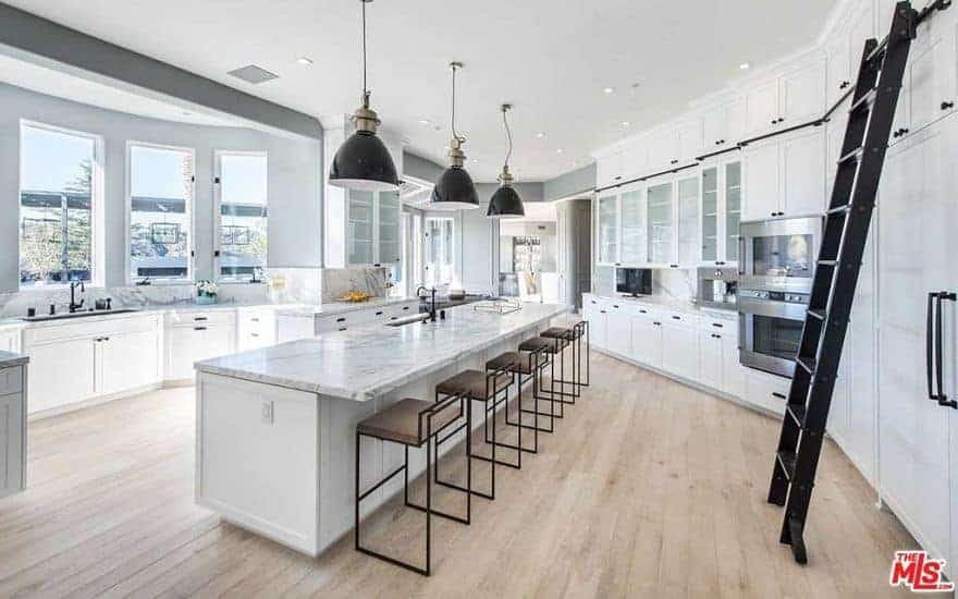 A bright kitchen featuring hardwood flooring and white kitchen counters and cabinetry. There's a long center island as well with a marble countertop and is lighted by three pendant lights.